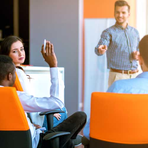 Employee raising their hand at an office procedure training to ask a question